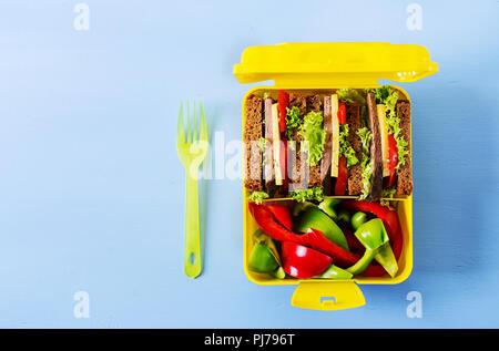 École en santé boîte à lunch avec sandwich au bœuf et légumes frais sur fond bleu. Vue d'en haut. Mise à plat Banque D'Images