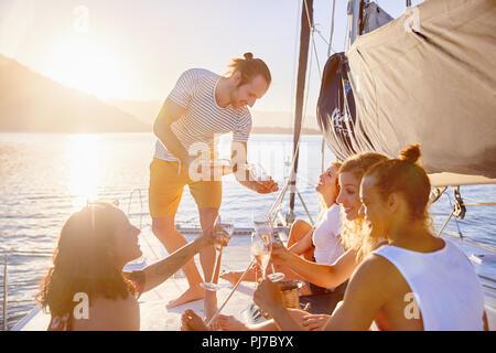 Friends drinking champagne sur catamaran ensoleillée Banque D'Images