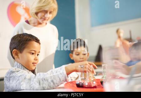 L'observation des enseignants étudiants curieux de jouer avec exposition interactive dans les béchers à science centre Banque D'Images