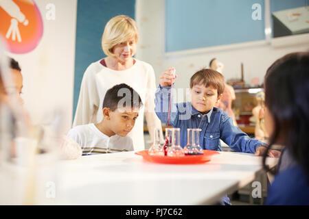 L'enseignant et les étudiants à la pipette et gobelets à l'exposition interactive dans science center Banque D'Images