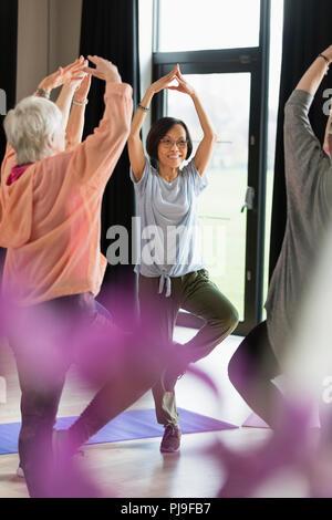Smiling senior woman practicing yoga, posture de l'arbre Banque D'Images