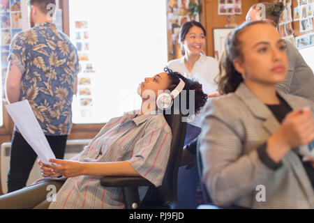 Creative businesswoman with headphones listening to music in office Banque D'Images