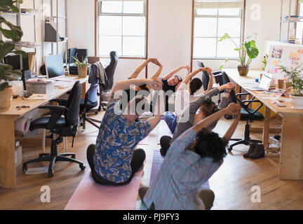 Creative business people stretching, pratiquant le yoga in office Banque D'Images
