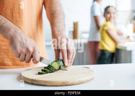 Cropped shot de concombre Salade de coupe père alors que sa femme et sa fille lave-vaisselle cuisine à Banque D'Images