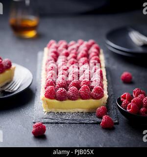 Tarte aux framboises avec la crème vanille et chocolat blanc sur ardoise. Arrière-plan de la pierre noire. Banque D'Images