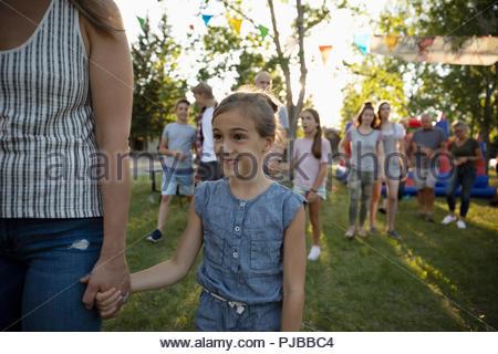 Smiling girl holding hands with mère au quartier d'été block party in park Banque D'Images