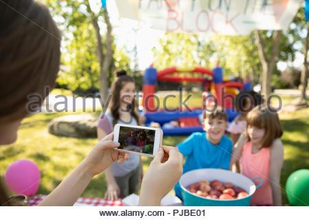 Femme avec téléphone appareil photo photographier les enfants dansant pour les pommes au quartier d'été block party in park Banque D'Images