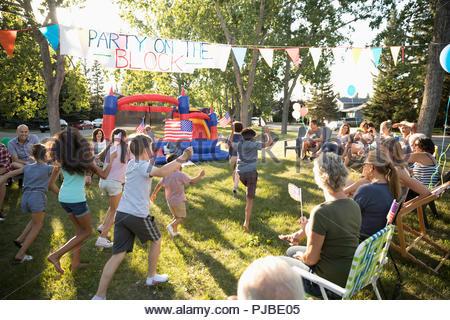 Des voisins qui surveillent les enfants agitant des drapeaux américains à l'été du 4 juillet fête de quartier en quartier sunny park Banque D'Images