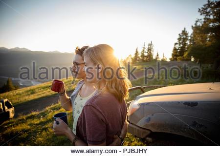 Couple de boire du café à côté de SUV, à la recherche de sunny, idyllique sur la montagne, de l'Alberta, Canada Banque D'Images