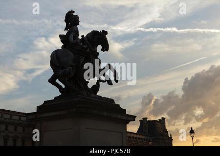 Statue équestre du roi Louis XIV de France par sculpteur baroque italien Gian Lorenzo Bernini devant le palais du Louvre (Palais du Louvre) à Paris, France, au coucher du soleil. Banque D'Images