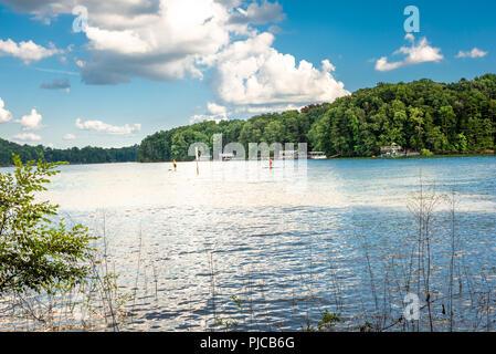 Jeune couple paddle dans le lac Lanier à côté des propriétés du secteur riverain Banque D'Images
