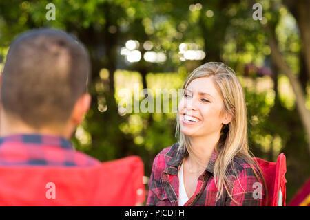 Couple parler et rire sur un voyage de camping. Banque D'Images