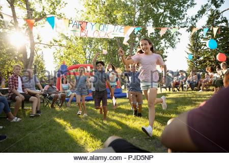 Enfants qui courent, agitant des drapeaux américains à l'été du 4 juillet fête de quartier en quartier sunny park Banque D'Images