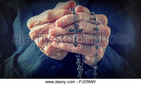 Mains d'un sage femme tenant un Rosaire en priant,Christian daily devotional d'un adorateur, relation avec Dieu le Créateur et Sauveur Banque D'Images