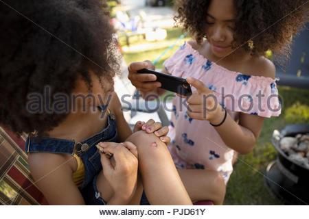 Fille avec téléphone appareil photo photographier avec soeur genou écorché Banque D'Images