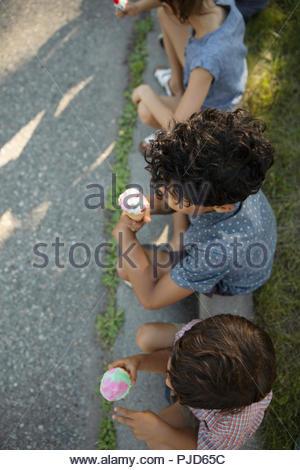 Vue de dessus les enfants de manger des glaces sur le trottoir Banque D'Images