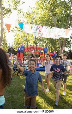 Enfants enthousiastes avec des drapeaux américains à l'été du 4 juillet fête de quartier en quartier sunny park Banque D'Images