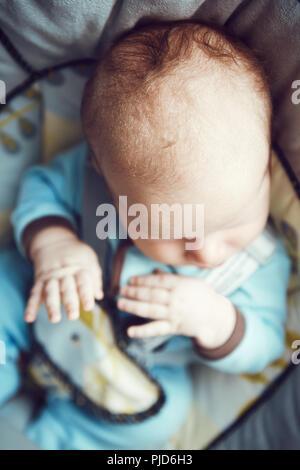 Portrait of cute adorable petit bébé garçon dormir caucasienne dans nouveau-né vêtements bleu assis dans balançoire, vue sur la tête de mains top abo