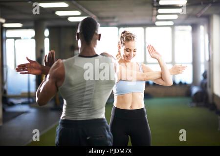 Formateur et female client doing stretching de l'exercice dans la salle de sport Banque D'Images