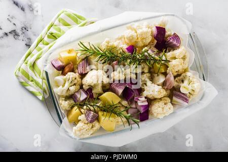 Les légumes d'automne dans un verre de cuisson: chou-fleur, les pommes de terre et oignons rouges. cuit saine des aliments dans le four. Banque D'Images