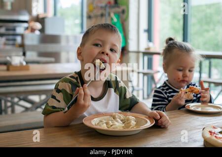 Les enfants peuvent manger des pizzas et de beignets de viande cafe. Les enfants de manger des aliments malsains à l'intérieur. Frères et sœurs dans le café, des vacances en famille concept. Banque D'Images