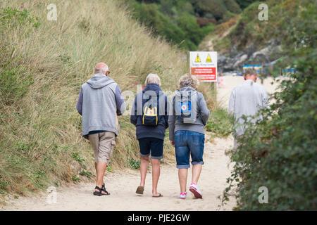 Les vacanciers matures marcher le long d'un chemin de plage de Crantock en Newquay Cornwall. Banque D'Images