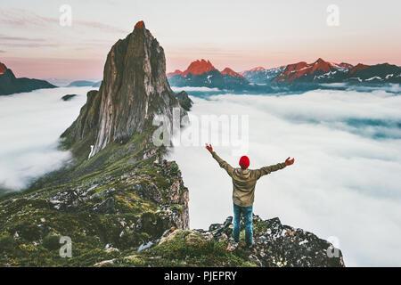 Traveler appréciant le coucher du soleil en plein air d'aventure Randonnées montagne Segla en Norvège vacances actives vie voyage homme haussa les mains sur les nuages au-dessus de falaise Banque D'Images