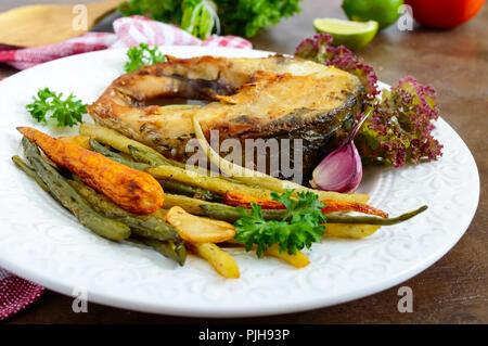 Steak de poisson frit avec légumes grillés sur une plaque blanche. Une bonne nutrition. Banque D'Images