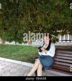 Portrait of middle-aged woman with glasses assis dans le parc sur un banc et regarder des photos sur l'écran de l'appareil. Banque D'Images