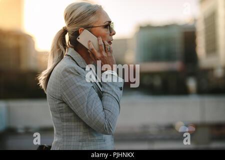 Vue latérale du professionnel d'affaires à l'extérieur de marche sur route talking on cell phone. Femme mature la marche à l'extérieur sur la rue avec mobile p