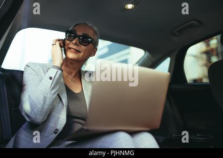 Femme entrepreneur voyageant à bureau dans une voiture de luxe assis sur la banquette arrière avec coffre et à l'extérieur de la fenêtre tout en parlant au téléphone . Ma Banque D'Images