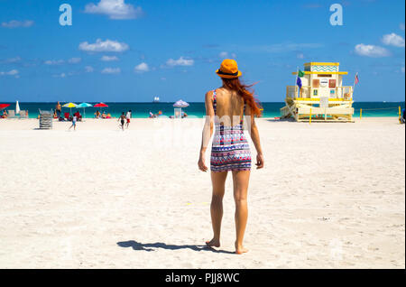 Maison de vacances à Miami Beach en Floride. Vue arrière de cheveux rouge femme en coupe tendance de l'été tenue, lifeguard Tower, les enfants et les gens de soleil, USA Banque D'Images