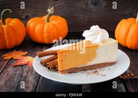 Tranche de gâteau au fromage à la citrouille avec crème fouettée sur un fond de bois rustique foncé