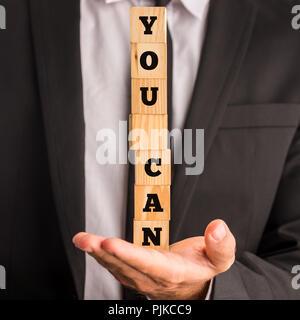 Portrait d'une pile de blocs dans la paume de sa main avec les mots - vous pouvez - dans un message de motivation et d'inspiration d'utiliser ceux