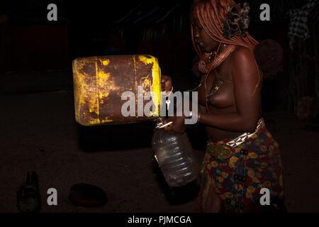Young woman pouring Himba, une rareté de l'eau de pluie recueillies en Namibie, d'une cartouche dans une bouteille en plastique