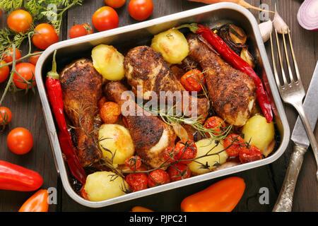 Cuisses de poulet rôti avec pommes de terre et les légumes sur le plateau Banque D'Images