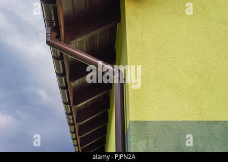 Façade de maison vert clair avec toit visible soffite et gouttière. Dans l'arrière-plan un beau ciel bleu avec des nuages. Banque D'Images