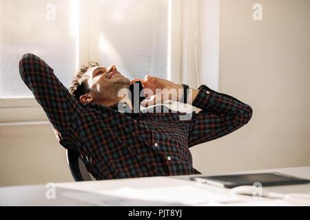 Relaxant du dos de l'entrepreneur sur sa chaise et on cell phone assis à son bureau. L'homme de prendre une pause du travail et talking on mobile phone leanin Banque D'Images