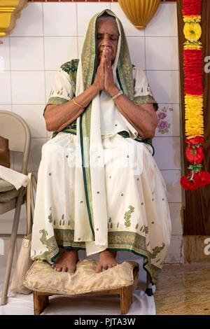 Une vieille femme hindoue prie et médite dans un temple dans le Queens, New York. Banque D'Images