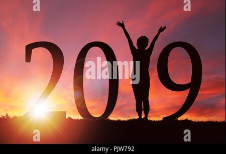 2019 Nouvelle année silhouette d'une fille avec les mains posées lors du lever ou du coucher du soleil d'or avec l'exemplaire de l'espace. Concept de joie, louange, adoration, liaison avec Banque D'Images