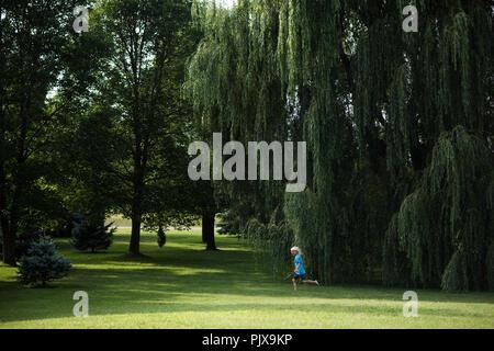 Garçon jouant sous willow tree Banque D'Images