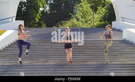 Trois sports pour aller sur les marches, l'un d'entre eux saute sur une corde Banque D'Images