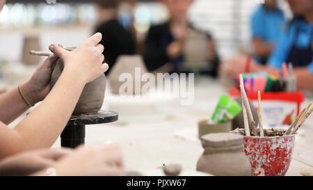 Les étudiants travaillant avec l'argile se salir les mains. La classe d'art visuel montrant les mains sur une bobine pot avec de l'argile outils et 24 en arrière-plan. Art educati Banque D'Images