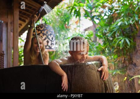 Happy Baby fils avec la mère s'amuser dans la baignoire. Femme enfant ludique la pulvérisation de douche à l'extérieur de la salle de bains sur véranda avec magnifique jardin tropical. Banque D'Images