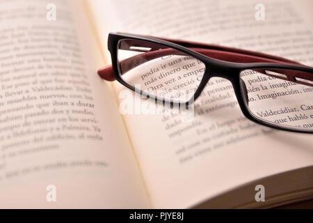 Détail de noir et rouge lunettes de lecture sur le livre ouvert.Concept besoin de lunettes pour lire. Vue élevée. Composition horizontale Banque D'Images