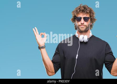 Handsome young man listening to music portant des écouteurs sur fond isolé vous détendre et souriant avec les yeux fermé faisant geste de méditation avec Banque D'Images