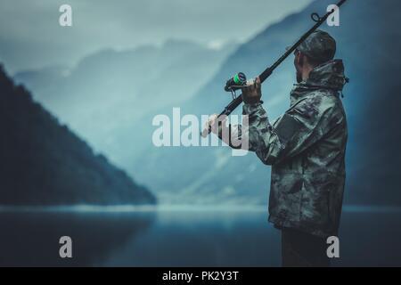 Pêche à la mouche en soirée. Caucasian Fisherman avec Canne à pêche sur la rive du lac glaciaire. Banque D'Images