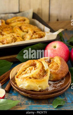 Petits pains frais Petits pains faits maison avec les pommes et la cannelle dans le glaçage sur un fond de bois vintage bleu. Banque D'Images
