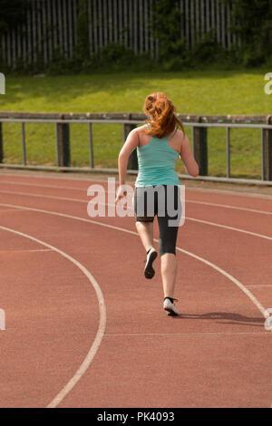 Athlétisme féminin s'exécutant sur la piste de sports Banque D'Images