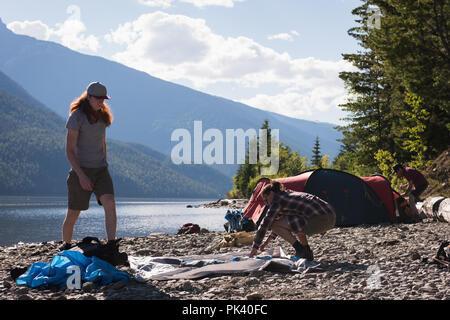 Couple setting up tent près de Riverside Banque D'Images